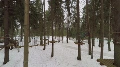 Stock Video Footage of Obstacle course with wooden beams on ropes in snowbound forest