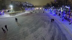 People skating by ice rink on Chistye Prudi at winter evening. Stock Footage
