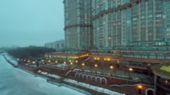Residential complex and illuminated quay on shore of icy river Stock Footage