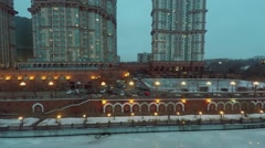 Residential complex on quay of icy river at winter evening Stock Footage