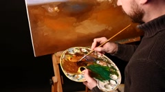 Talanted painter, dark sweater starts drawing an object on painting by oil Stock Footage