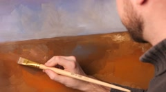 Talanted painter, dark sweater continues drawing a ground on painting by oil Stock Footage