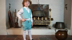 Little boy in medieval costume stands near fireplace Stock Footage