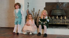 Two boys and girl in medieval costumes are near fireplace Stock Footage