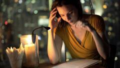 Young woman reading menu sitting on terrace in cafe at night HD Stock Footage