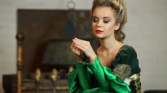 Young woman in luxury green medieval costume near fireplace Stock Footage