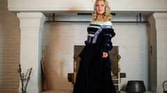 Beautiful woman in medieval costume dances near fireplace Stock Footage