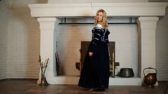 Pretty woman in medieval costume dances near fireplace Stock Footage