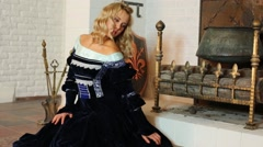 Pretty woman in medieval costume sits near fireplace Stock Footage