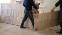Legs of workers carrying big cardboard boxes into room Stock Footage