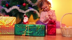 Smiling little girl sits with candle under decorated fir-tree Stock Footage