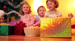 Two happy little girls and boy near christmas tree in room Stock Footage