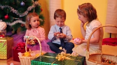 Two little girls and one boy sit near christmas tree and eat Stock Footage