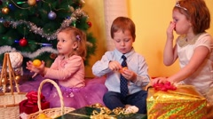 Two little girl and boy sit near christmas tree and eat tangerines Stock Footage