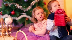 Little girl and boy sit under christmas tree, boy shakes red gift box and hears Stock Footage