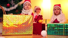 Three children in santa caps sit on furry rug under christmas tree - stock footage