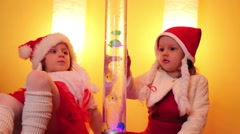 Three children in santa caps sit and look at decorative lighting Stock Footage