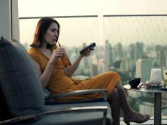 Young woman with smartphone drinking cocktail on terrace in cafe  NTSC Stock Footage