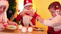 Two girls and boy paint on cookies near christmas tree Stock Footage