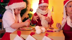 Two little girls and one boy in santa caps eat cookies at table - stock footage