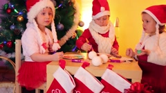 Two little girls and one boy paint on cookies and eat - stock footage
