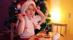 Little girl sits at table near christmas tree and hides in cap Stock Footage