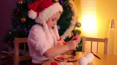 Little girl in santa cap paints on cookies near christmas tree Stock Footage