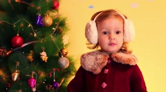 Little girl plays with artificial butterfly near christmas tree Stock Footage