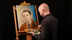 Talanted painter paints a picture of man by oil paint brush with palette in his Stock Footage