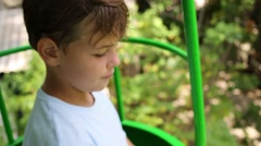 Boy teen in wagon of moving cableway above green trees Stock Footage