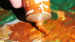 Painter squeezes orange oil paint on a palette, close up Stock Footage