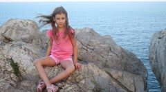Pretty girl in pink sits on rock near blue sea in windy day Stock Footage