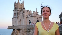Beautiful woman face near old castle on rock, tourists and  sea Stock Footage