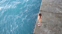 Above view of girl standing on concrete pier near sea water Stock Footage
