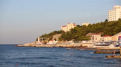 Coast line and piers and people near blue sea at summer Stock Footage