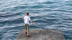 Boy with fishing rod fishes in sea and stands on concrete place Stock Footage