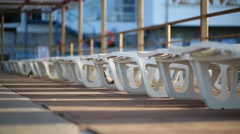 Grey pigeons walk near deck chairs outdoor at sunny day Stock Footage