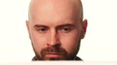 Bearded, bald artist painting something and evaluates it on white background Stock Footage