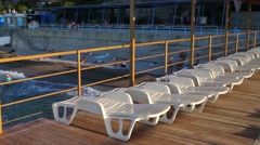 White plastic deck chairs on pier and resting people at evening Stock Footage