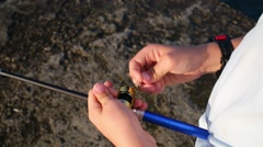 Hands of fishing boy with wrist watch rewinding line Stock Footage