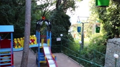 Cableway among green trees and children playground Stock Footage