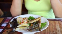 Rice with vegetables and fresh grilled fish on plate and hands Stock Footage