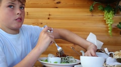 Boy eats grilled meat by fork and knife in cafe with wooden walls Stock Footage
