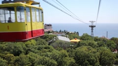 Stock Video Footage of Wagon of ropeway and sea coast. View from moving ropeway wagon