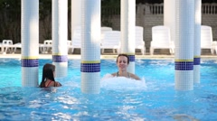 Smiling woman and girl swim in pool with Jacuzzi and rotunda Stock Footage