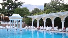 People rest near open pool in Marat Hotel in Yalta. Stock Footage