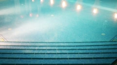 Stairs in empty blue swimming pool at summer night Stock Footage