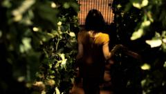 Woman walking down on stairs through plants at night HD - stock footage