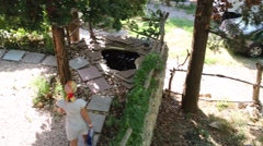 Top view of woman walking in garden with water source at summer Stock Footage