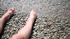 Female barefoot legs on pebble lapped by the waves of sea Stock Footage